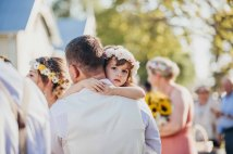 A groom hugs his daughter after the wedding